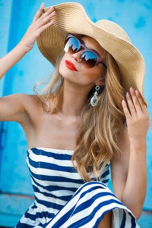 时尚的肖像。微笑的金发女人在时尚的外观。海洋风格。在蓝色的背景上。风格和热女孩户外。戴墨镜和草帽的女人。时尚。