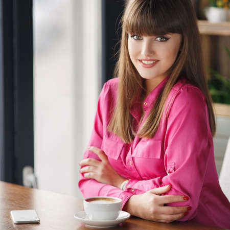thick hair: Girl with a Cup of hot tea at a table in a cafe.Portrait of a young beautiful brunettes with thick hair, low fringe, green eyes, beautiful smile, dressed in a red pullover with a white Cup of tea, sitting at a table in a cafe