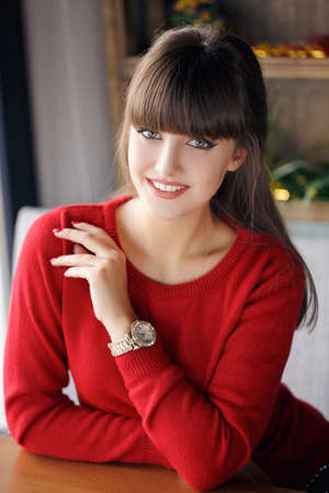 thick hair: Home portrait of beautiful young woman.Portrait of a young beautiful brunettes with thick hair, low fringe, green eyes, beautiful smile, dressed in a red sweater, posing for the photographer sitting at a table in a cafe