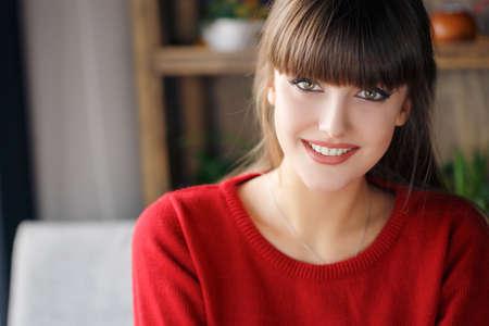 Accueil portrait de la belle jeune woman.Portrait d'une belle jeune brunes aux cheveux épais, à faible marge, yeux verts, beau sourire, vêtu d'un pull-over rouge, posant pour le photographe assis à une table dans un café