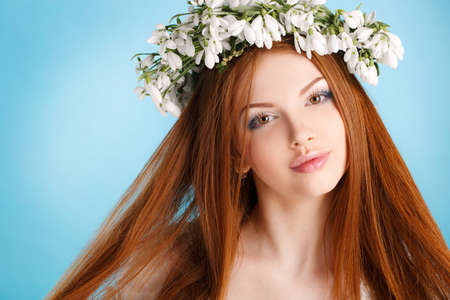 sleeveless dress: Beautiful girl with long red hair, brown eyes, light makeup, dressed in a white sleeveless dress, very beautiful on her head a wreath of white flowers forest snowdrop, closeup portrait in Studio on blue background