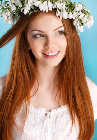 Beautiful girl with long red hair, brown eyes, light makeup, dressed in a white sleeveless dress, very beautiful on her head a wreath of white flowers forest snowdrop, closeup portrait in Studio on blue background