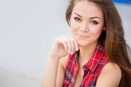 Summer portrait of beautiful young brunette with long straight, lush hair, brown eyes and a beautiful smile, piercings, dressed in a red plaid tank top, posing for the photographer sitting on the stairs in the city in the summer.