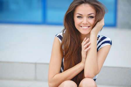 person outdoors: Summer portrait of a beautiful young brunette woman with long straight hair, brown eyes, wearing a sailors striped shirt and dark blue shorts, posing in summer, sitting against the backdrop of the beautiful white building with large blue windows