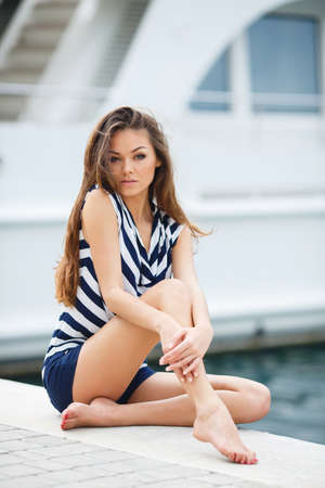yacht club: Beautiful girl, brunette with long straight hair, brown eyes, wearing a striped shirt with blue and white stripes and dark blue shorts, posing for a photograph near the yacht club, sitting on a pier in the background of the sea and beautiful yachts.