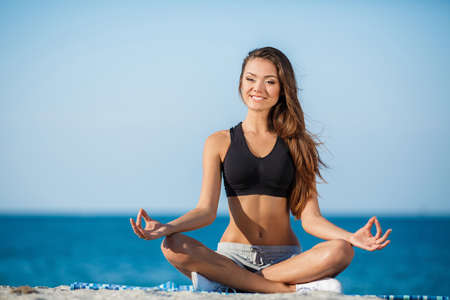 Young beautiful brunette woman with long straight hair and brown eyes, a short black shirt, gray shorts and white sports shoes, meditating on the beach in a lotus position on the background of the ocean.