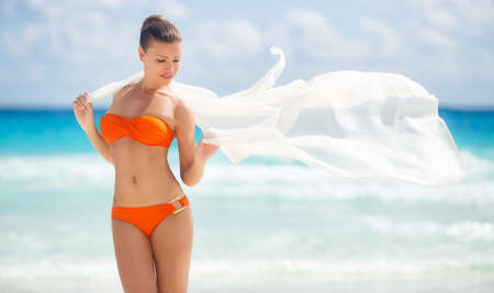 A woman with a beautiful figure, a brunette with stylish hair, in an orange bikini, with a light transparent white pareo for the beach, thrown over shoulder, posing near the blue ocean while standing on a white sand tropical beach