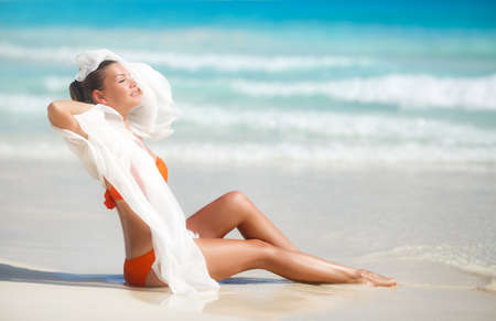 pareo: A woman with a beautiful figure, a brunette with stylish hair, in an orange bikini, with a light transparent white pareo for the beach, thrown over shoulder, posing near the blue ocean while standing on a white sand tropical beach