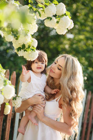 summer wear: Happy mother, with long blonde hair and brown eyes, with her little daughter in her arms, stand against the fence, next to a blossoming white flowers of the Bush in the village in summer, wear with white dresses