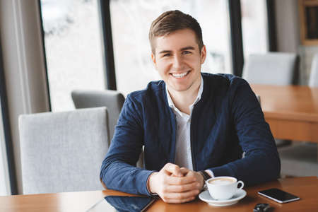 Junger Mann, dunkle Haare mit braunen Augen, ein weißes Hemd und eine dunkelblaue Jacke, eine Armbanduhr auf seiner linken Hand tragen, an einem Tisch gegenüber dem Fenster, auf dem Tisch-Tasse Kaffee, Tablet-Computer, Smartphone sitzt in einem Café und elektronische Schlüssel