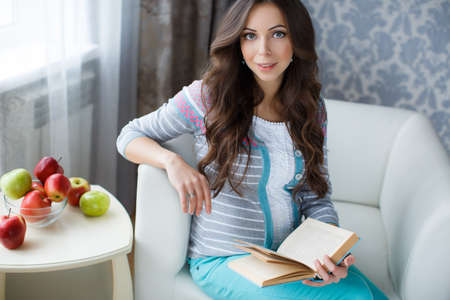 thick hair: Pretty young pregnant woman, brunette with long thick hair and gray eyes, dressed in a gray sweater and turquoise pants, sits in a white armchair in her room, hands holding a book, next on the table are apples Stock Photo