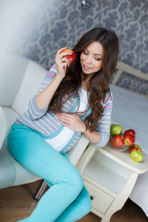 gray eyes: Beautiful young pregnant woman with apples.Pretty young pregnant woman, brunette with long thick hair and gray eyes, dressed in a gray sweater and turquoise pants, sits in a white chair in his room, in his hand holding a red Apple Stock Photo