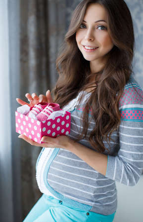 adult pregnant: Beautiful young pregnant woman, brunette with long thick hair, wearing a gray striped sweater and turquoise pants, on the right-hand engagement ring, holding a pink box with white polka dots with pink booties in it