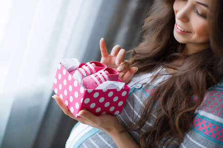 pregnant: Beautiful young pregnant woman, brunette with long thick hair, wearing a gray striped sweater and turquoise pants, on the right-hand engagement ring, holding a pink box with white polka dots with pink booties in it