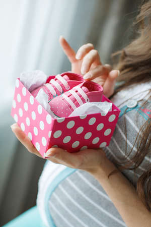 thick hair: Beautiful young pregnant woman, brunette with long thick hair, wearing a gray striped sweater and turquoise pants, on the right-hand engagement ring, holding a pink box with white polka dots with pink booties in it