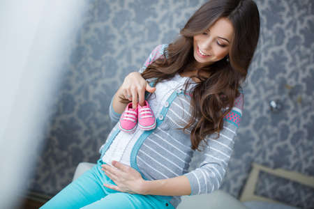 beautiful    baby: Beautiful young pregnant woman, a brunette with long hair, dressed in a gray sweater and blue pants, right hand wedding ring, holding pink booties for the baby, putting them on his big bare belly Stock Photo
