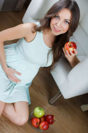 thick hair: Beautiful young pregnant woman with apples.Pretty young pregnant woman, brunette with long thick hair and gray eyes, dressed in a white nightgown, sitting on the floor beside the chair white in his room, in his hand holding a red Apple