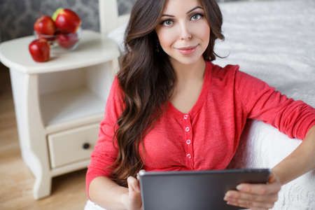 thick hair: Pregnant woman, brunette with long thick hair, a nice smile and light makeup, wearing a red shirt and white pants, on the right-hand engagement ring, spending time in his bedroom, working with a tablet in Internet next on the table are apples