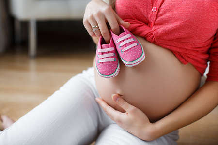 big shirt: Beautiful young pregnant woman, brunette with long thick hair, wearing a red shirt and white pants, right hand wedding ring, holding pink booties for the baby, putting them on his big bare belly