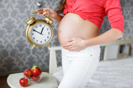 thick hair: Pregnant woman, brunette with long thick hair, a nice smile and light makeup, wearing a red shirt and white pants, spends his time in his bedroom, in one hand holding a big alarm clock, the other hand supports the belly