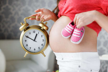 thick hair: Beautiful young pregnant woman, brunette with long thick hair, wearing a red shirt and white pants, right hand holding a big alarm clock in his left hand holding pink booties for the baby, putting them on the stomach