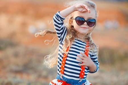 anteojos de sol: La niña en el prado con hierba seca en la niña feliz summer.A, morena con el pelo largo y rizado, vestido con una camisa de rayas marineras y una falda tejida en gafas de sol oscuras, de pie en una playa rocosa.