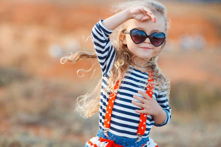 sunglasses beach: The little girl on the meadow with dry grass in the summer.A happy little girl, brunette with long curly hair, dressed in a striped sailor shirt and a knitted skirt in dark sunglasses, standing on a rocky beach.