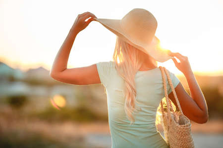 admiring: Woman in hat with large fields, at sunset.A slender woman, with long blonde hair in a straw hat with large brim, blue shorts and blue t-shirt, on the shoulder woven straw bag, admiring the sunset while standing on the beach near the sea Stock Photo
