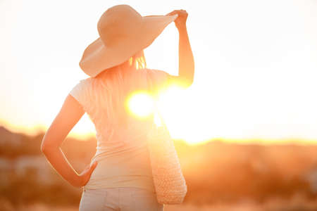 Woman in hat with large fields, at sunset.A slender woman, with long blonde hair in a straw hat with large brim, blue shorts and blue t-shirt, on the shoulder woven straw bag, admiring the sunset while standing on the beach near the sea Stock Photo