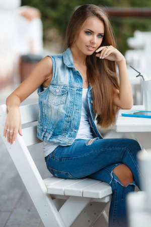 straight jacket: Happy young woman with long straight hair, brunette with blue eyes, beautiful makeup, dressed in a blue denim jacket without sleeves, poses for a photograph in the open air in the summer, sitting at a white table in a cafe