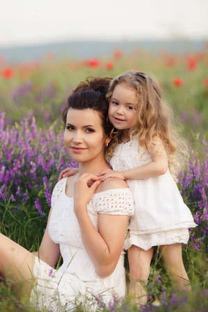 mother care: A beautiful young woman, a brunette, with her small daughter, a girl with long wavy, blond hair, both dressed in white dresses, spend time together on a mountain meadow among the blossoming lilac lavender outdoors in summer