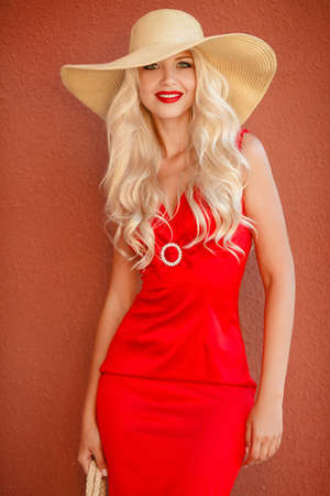 flyaway: Beautiful blonde with long, thick, curly hair and gray-green eyes, beautiful makeup and red lipstick, a yellow straw hat with large brim, dressed in a red summer dress, posing on a pink background near the house