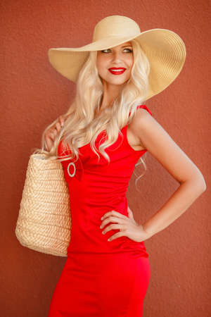 flyaway: Beautiful blonde with long, thick, curly hair and gray-green eyes, beautiful makeup and red lipstick, a yellow straw hat with large brim, dressed in a red summer dress, holds wicker bag straw, posing on a red background