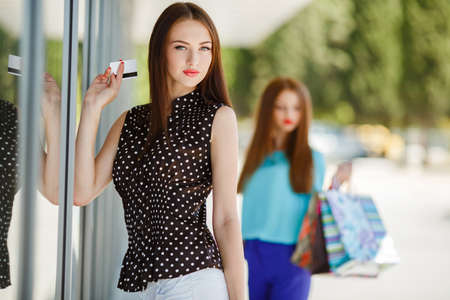 gray eyes: Slender beautiful woman, brunette with long straight hair and gray eyes, wearing a black blouse with white polka dots, spending time in the supermarket with colorful shopping bags and credit cards, resting and shopping