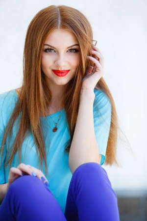 Young beautiful woman with long red hair and brown eyes, red lipstick and blue nail polish, wearing a blue blouse and blue pants, a beautiful smile, on the neck is a medallion portrait of summer against a white wall in the open air Stock Photo