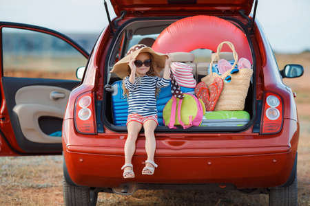 Little girl, brunette with long curly hair, dressed in a striped sailors shirt, dark sunglasses and a large straw hat, goes on a journey to the sea, sits in the trunk of the red car loaded with suitcases and bags Stock Photo
