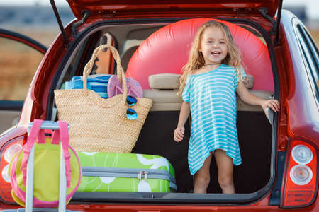 Portrait of a little girl sitting in the trunk of a car.Little girl, brunette with long curly hair, dressed in a blue summer dress, goes on a journey to the sea, sits in the trunk of the red car, loaded, suitcases and bags, pink lifeline Stock Photo