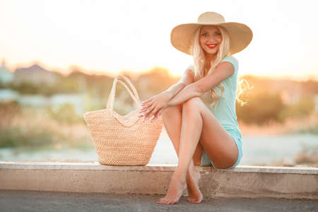 Bright blonde in beautiful hat in the rays of the setting sun.A slender woman, with long blond hair in straw hat with large brim, blue shorts and blue t-shirt, standing next to the bag, watching the sunset, sitting on the beach near the sea