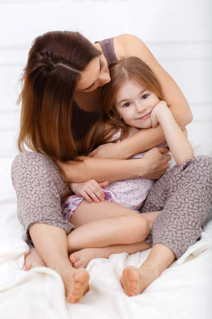 Young beautiful woman brunette with long hair and brown eyes, together with his daughter, a girl of 6 years, brown hair, brown eyes, dressed in a t-shirt and panties, to spend time together in the bedroom, sitting on white bed