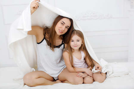Young beautiful woman brunette with long hair and brown eyes, together with his daughter, a girl of 6 years, brown hair, brown eyes, dressed in a t-shirt and panties, to spend time together in the bedroom, playing on a white bed , covered by sheets Reklamní fotografie