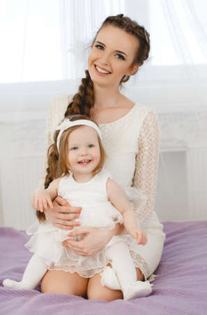 gray eyes: Happy family, young beautiful woman with dark hair, in a braid, gray eyes, dressed in a white lace dress, playing with his little daughter, girl - a brunette with short hair, in the bedroom on the bed with purple blanket
