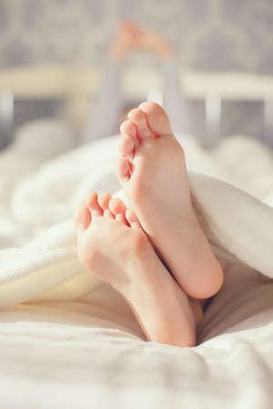 piedi nudi di bambine: Piedi bambino su manto bianco sul letto. Adorabile bambina si sveglia nel suo letto. mattina. Ritratto dei piedi dei bambini in camera da letto Archivio Fotografico