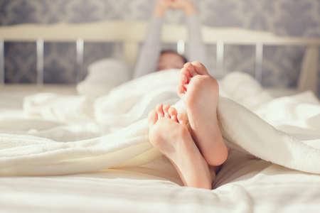 ベッドの上の白い毛布に子供の足。かわいい女の子を彼女のベッドで目覚め。朝。寝室は子供のフィートの肖像画 写真素材