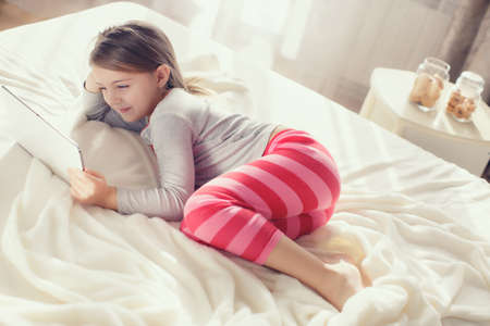 nice girl: The nice little girl of 6 years, the brunette with soft hair, in pink striped pajama trousers and a gray t-shirt, lying on the bed covered with a fluffy white cover communicates with friends on social networks, using the tablet computer of white color