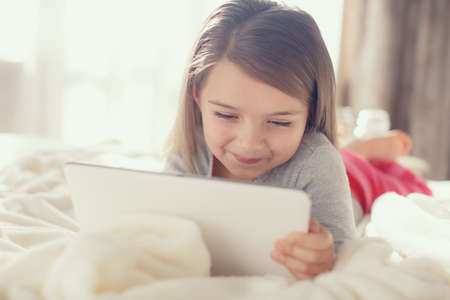 The nice little girl of 6 years, the brunette with soft hair, in pink striped pajama trousers and a gray t-shirt, lying on the bed covered with a fluffy white cover communicates with friends on social networks, using the tablet computer of white color