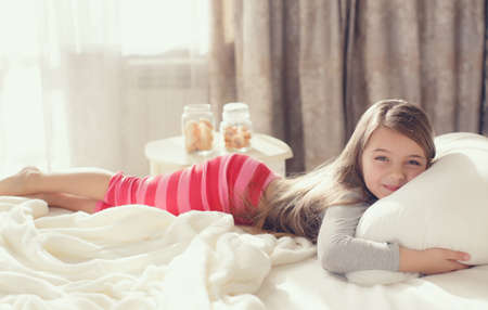 Morning portrait of a little girl waking up, embracing the pillow.Little girl, brunette in pink striped pajama bottoms and a gray t-shirt, wakes up in the morning in a white bed in the bedroom, tightly hugging a big soft pillow, lying on the bed