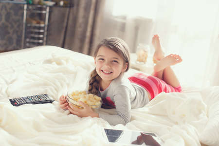 The pretty little girl of 6 years, the brunette with the long hair braided to the spit is dressed in a gray t-shirt and pink striped trousers, spends the time of the house, lies on a white bed near a window with the control panel the TV in one hand, eats