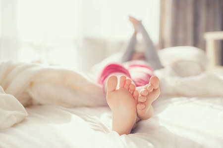 Child feet on white blanket on bed. Adorable little girl awaking up in her bed. morning. Portrait of a children's feet in the bedroom