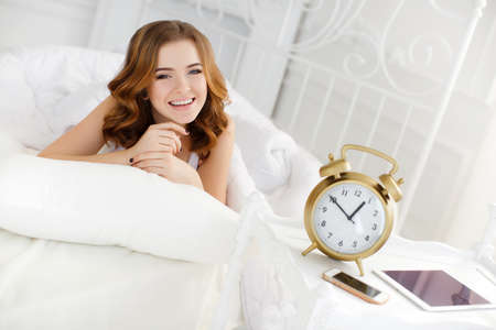 night shirt: Beautiful girl wakes up in a white bed in the morning.Young beautiful redhead woman with long curly hair and gray eyes, a white night shirt, wakes up in the morning on a soft pillow in a white bed in the bright bedroom with vintage white bed