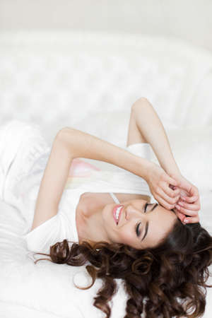 night shirt: Happy young woman wakes up in a white bed in the morning.Young beautiful woman brunette with long curly hair, in a white night shirt, wakes up in the morning on a soft pillow in a white bed in bright bedroom